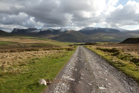 A rough track cuts through moorland towards a cloudy Nantlle ridge in the Snowdonia national park, Wales, UK.