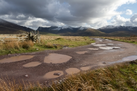 A rough track with water filled potholes cuts through moorland towards a cloudy Nantlle ridge in the Snowdonia national park, Wales, UK.