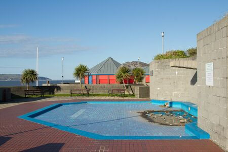 enclosed: An unused childrens paddling pool, blue and red tiled, in an enclosed area with benches and trees.