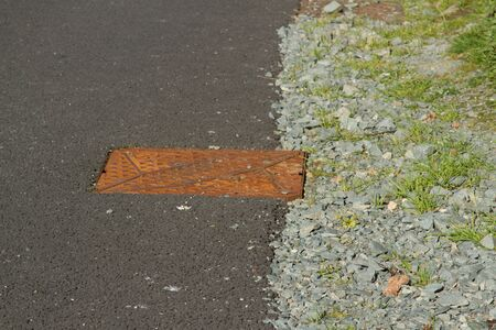 hardcore: A tarmac road  path and edging hardcore with a rusty metal drain cover. Stock Photo