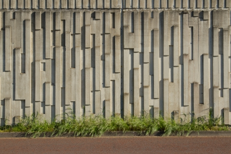 precast: A precast concrete wall patterned with vertical oblong textures with green grass on a horizontal plane and a red tarmac path below.