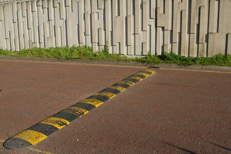 A black and yellow speed bump, rumble strip stretches across a red tarmac road. Stock Photo