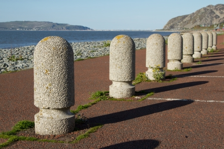 precast: A set of concrete precast parking bollards stretch into the distance with a path, pebble beach and the sea in the distance.