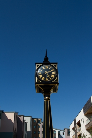 roman pillar: A clock with roman numerals on a post, pillar, painted black and gold with generic housing and a blue sky as a background. Stock Photo