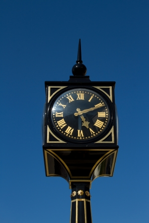roman pillar: A clock with roman numerals on a post, pillar, painted black and gold with a clear blue sky in the background.