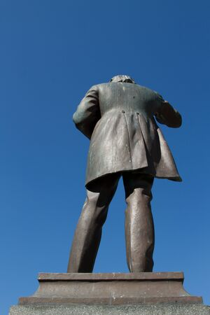 frock coat: The rear view of a statue cast in bronze on a slate plinth with a man gesticulating in a frock coat against a clear blue sky.