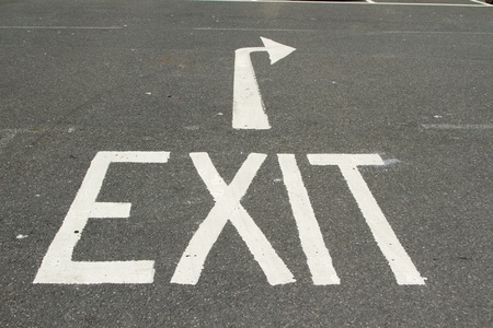 exit sign: A tarmac road with the word, EXIT and a directional arrow painted in white.