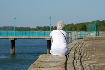 A middle aged, elder woman with short white hair, a white blouse and shoulder strap sits on a wall staring into the distance next to the sea. Stock Photo