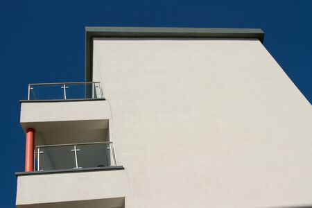 A building painted cream with a flat roof and balconies with a post, railings and glass panels against a blue sky.