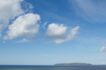 A sea view with an island in the distance under a big sky with large fluffy clouds. Stock Photo