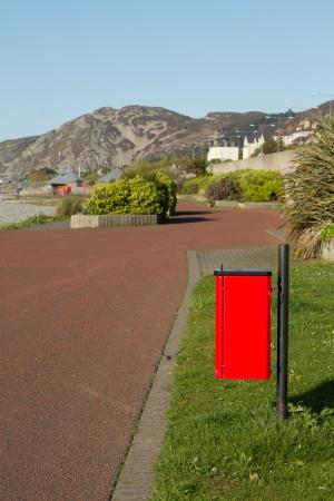 faeces: Un bidone rosso su un post per escrementi di cane, le feci, accanto a un sentiero con bordi erba e una collina in lontananza. Archivio Fotografico