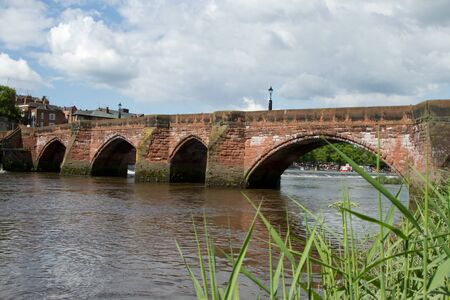 An historic red sandstone bridge with arches and a flowing river against a sky with cloud.