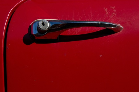 A red car door with a vintage metal handle and push button opener with a key hole lock. photo