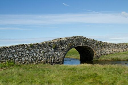 An historic narrow stone built bridge crossing a river with green grass and a blue cloudy sky in the distance.