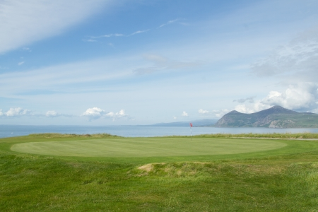 A putting green with tended grass and flag pole marker overlooking the sea and distant mountains. Stock Photo