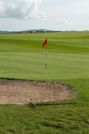 A sand bunker with rake next to a putting green with marker flag with a grey cloudy sky in the distance. photo