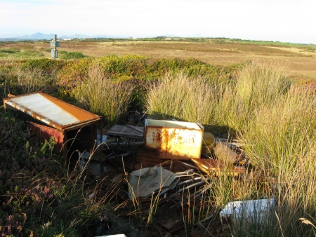 An area of moorland countryside with a pile of illegal rubbish rusting amongst grasses.