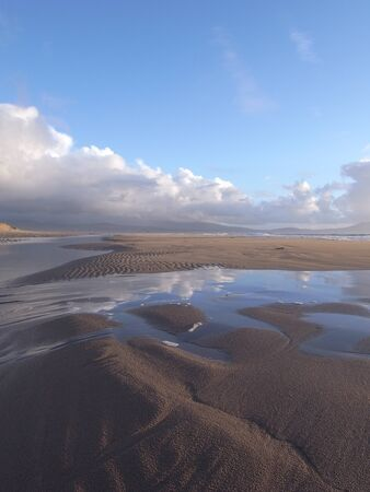 A sandy beach with rippled sand and a dune with the tide bringing the sea over the sand with reflections of a blue cloudy sky.