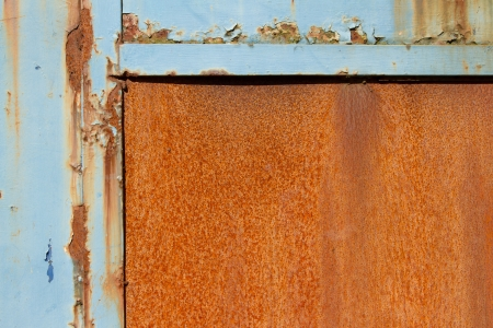 A rusty metal sheet with a half frame of blue damaged flaking paint. Stock Photo