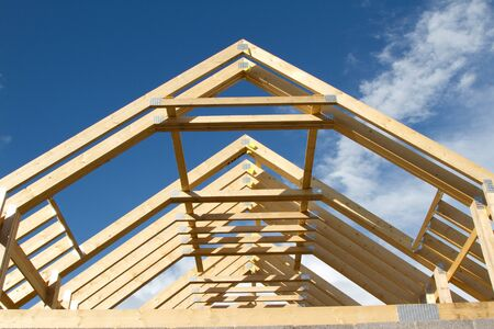 rafters: A new build roof with a wooden truss framework making an apex against a blue sky with cloud.