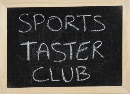 taster: A blackboard with a wooden border with the words SPORTS TASTER CLUB written by hand in white chalk.