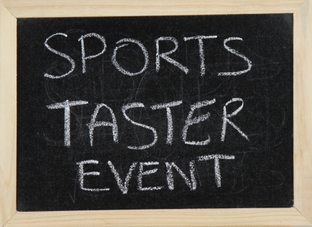 taster: A blackboard with a wooden border with the words SPORTS TASTER EVENT written by hand in white chalk. Stock Photo