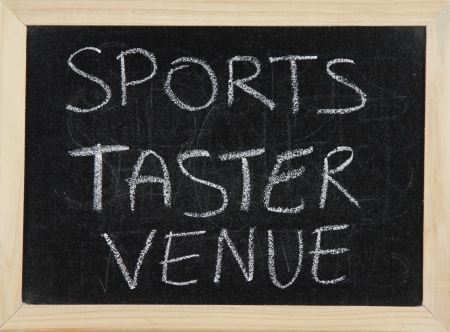 taster: A blackboard with a wooden border with the words SPORTS TASTER VENUE written by hand in white chalk.