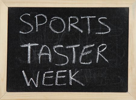 taster: A blackboard with a wooden border with the words SPORTS TASTER WEEK written by hand in white chalk. Stock Photo
