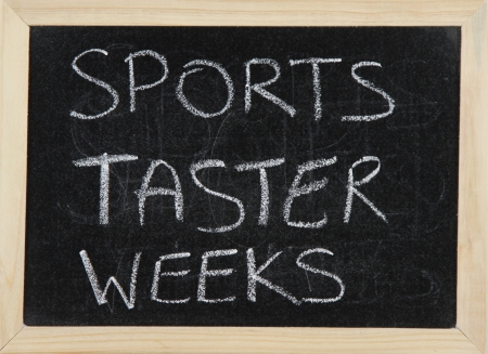 taster: A blackboard with a wooden border with the words SPORTS TASTER WEEKS written by hand in white chalk. Stock Photo