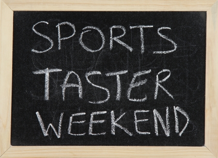 taster: A blackboard with a wooden border with the words SPORTS TASTER WEEKEND written by hand in white chalk.