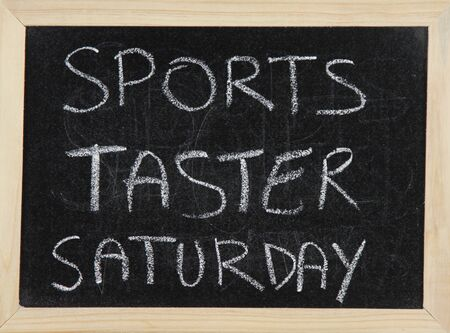 taster: A blackboard with a wooden border with the words SPORTS TASTER SATURDAY written by hand in white chalk.