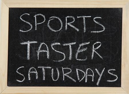 taster: A blackboard with a wooden border with the words SPORTS TASTER SATURDAYS written by hand in white chalk. Stock Photo