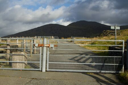 A road with locked metal security gates with mountains in the background. Stock Photo - 15481194
