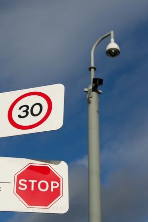 A pair of signs on a white background with a 30 speed limit and a stop warning overlooked in the background by a cctv camera. Stock Photo
