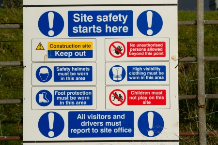 A white board with symbols and warnings explaining site safety rules and precautions.