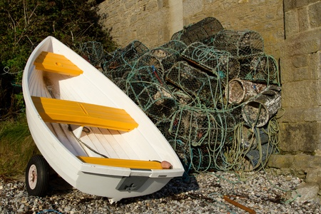 crab pots: A white boat, dinghy, out of water next to a pile of lobster and crab pots.
