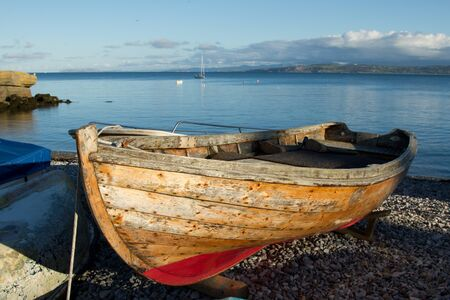 A wooden boat out of water on a pebble beach with the sea and blue sky in the distance