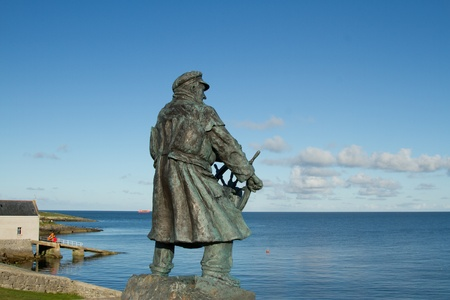 lifeboat station: The bronze statue of a sea captain in coat and hat holding a ships wheel looking out to sea with a lifeboat station and ramp in the background.