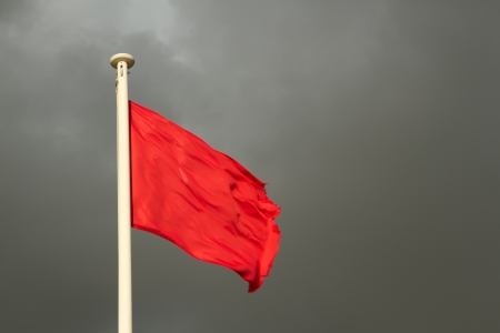 A white flag pole with a bright red flag against a grey cloudy sky.