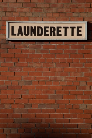 launderette: A red brick wall with a sign and the words LAUNDERETTE written in black.