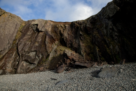 A pebble shore leads to a rock fall under a shale cliff with a blue sky and cloud in the distance. Stock Photo - 17574543