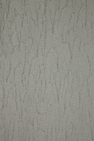 granular: Wall with grey textured granular spray paint in excess with runs.