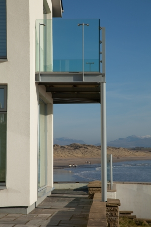 A first floor balcony with glass railings overlooks the sea and beach with surfers at the shore and dunes leading to mountains in the distance.