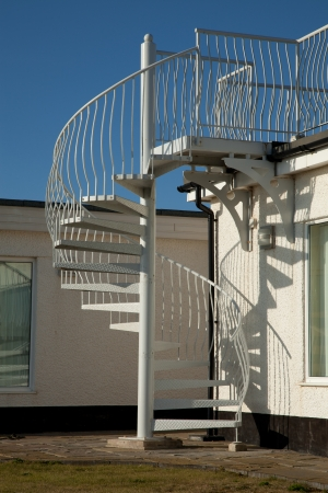 An exterior set of metal spiral stairs leading from a path to a balcony with a blue sky in the background.