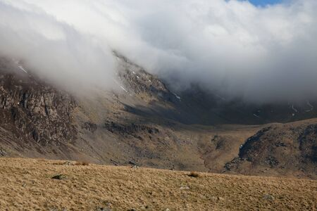 inversion: A developing cloud inversion creeps down the rocky mountainside into the valley.