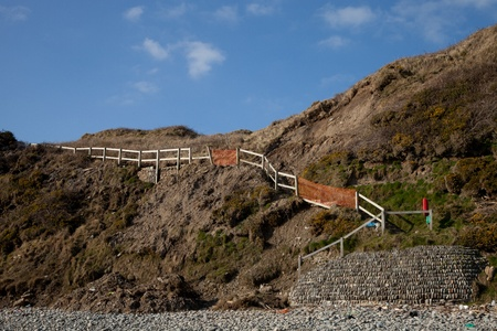 A steep grass bank with a mudslide and damage to a set of steps leading to a beach.