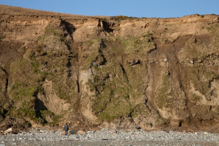 A man stands and looks up under a steep bank with areas of landslide errosion. Stock Photo