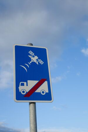 A sign with a lorry, truck, and red slash with a satellite tracking symbol above, on a blue background against a blue sky with cloud Stock Photo