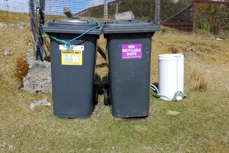 organics: A pair of waste bins with colour coded signs, yellow with the words ORGANICS ONLY and purple with NON RECYCLABLE WASTE on grass infront of a fence.