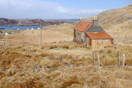 An old derelict building on moorland with tin roof and shed attached and a view to the sea and distant hills.